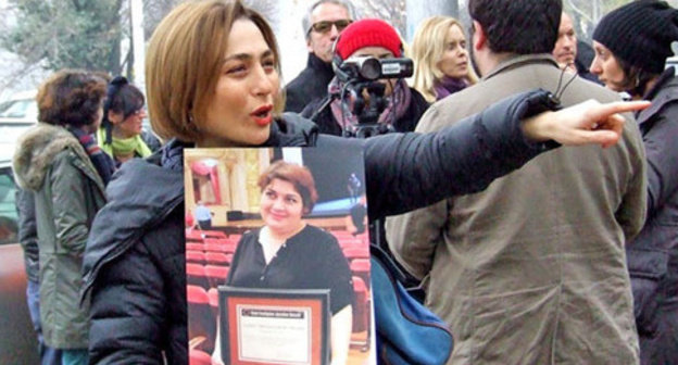"Nino Daneliya, a participant of the action, holds a poster with the photo of the journalist Khadija Ismayilova. Tbilisi, December 10, 2014. Photo by Edita Badasyan for the ""Caucasian Knot"