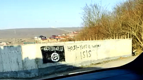 "An image of the flag used by the militants of the ""Islamic State"" (recognized on December 29, 2014, by the Supreme Court of the Russian Federation as a terrorist organization) on a wall of the building in the village of Khosi-Yurt. Photo: screenshot of a video ISIS in Khosi-Yurt / IG in Chechnya, http://www.youtube.com/watch?v=n2sVCqLfPp0"
