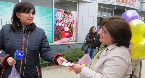 Woman gives out leaflets inviting to the action of Women's Resource Centre in Stepanakert. Photo by Alvard Grigoryan for the 'Caucasian Knot'.