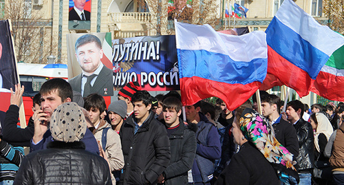 Students hold flags and Kadyrov's potraits durign rally on Day of Unity in Grozny, November 4, 2015. Photo by Magomed Magomedov for the 'Caucasian Knot'.