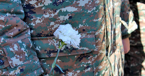 White carnation in the hands of soldier. Photo by Alvard Grigoryan for the 'Caucasian Knot'.