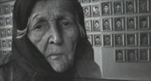 An elderly woman near the photos of the victims of war and deportation. Photo: screenshot of the video on the YouTube channel vainakh38