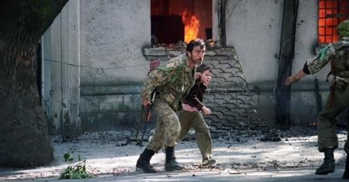 Fighter is taking a child away from the burning building in Sukhumi, 1993. Photo: Andrei Soloviev, RFE/RL