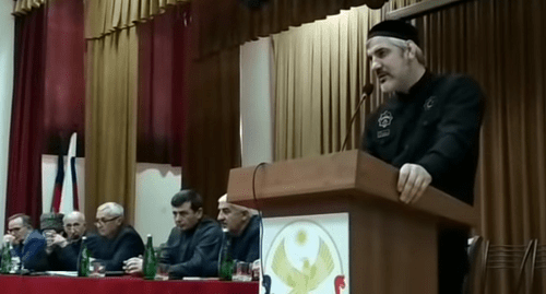 "Buvaisar Saitiev (behind the podium) and participants of the Congress of Chechens of Dagestan held in Khasavyurt. Photo: screenshot of the video by the ""Chernovik"" (Draft) https://www.youtube.com/watch?v=1QYyCCeOl0I"