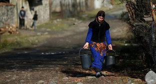 A woman carrying buckets of water in a street of a village Tsinubani in Pankisi Gorge, Georgia. Photo: REUTERS: David MdzinarishviliHEADLINE:A