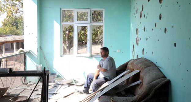 "A local resident sitting in a house damaged by shelling. October 20, 2020. Photo by Aziz Karimov for the ""Caucasian Knot"""