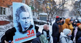 "A man holds a poster with the words ""For Navalny!""; people standing near the police station where Russian opposition leader Alexei Navalny is being held. Moscow, January 18, 2021. Photo: REUTERS / Maxim Shemetov"