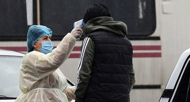 Medical worker measuring temperature. Photo: Hayk Baghdasaryan/Photolure via REUTERS