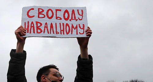 A protestor holding banner in support of Alexei Navalny. Abstract illustration. Photo: REUTERS/Anton Vaganov